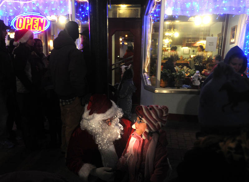 Santa Claus listens carefully to Laura Harding, 3, of Harmony, offer a list of gifts she would would like to see under her Christmas tree this year, while at the Parade of Lights on Water Street in downtown Skowhegan earlier this month.