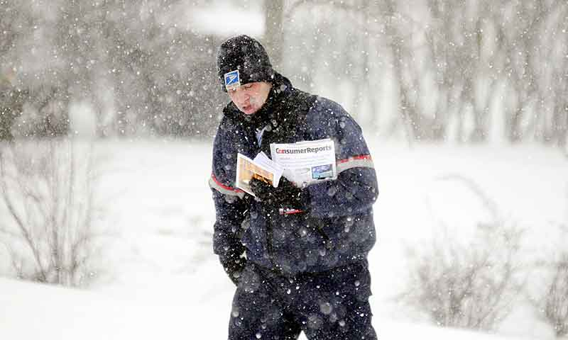 Mail carrier Devin Saban delivers mail Thursday in Hallowell, just as the storm begins to move through the area. Several inches are forecast and all state offices are closed.