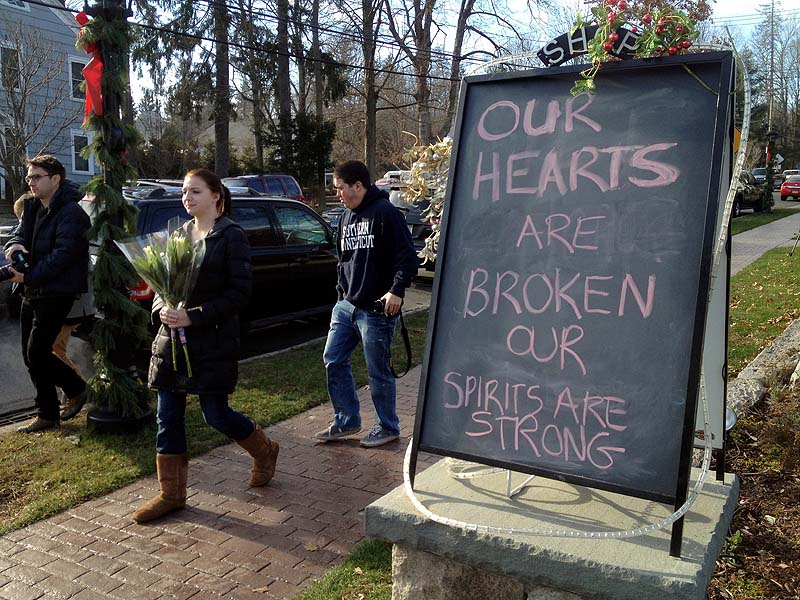 Jessica Henderson, 19, walks past a sign with a bouquet of flowers to lay at a memorial at The Sandy Hook School in Newtown, Conn., on Saturday.
