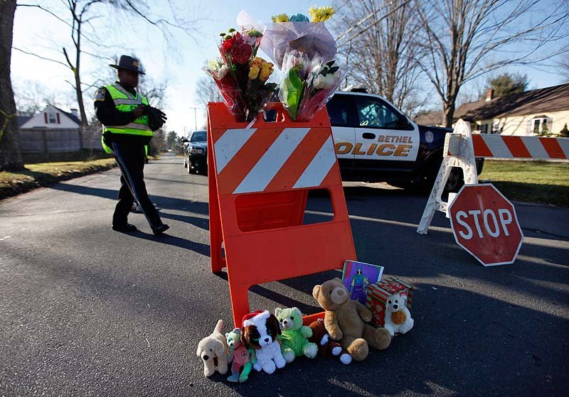 A police roadblock serves as a makeshift memorial at the corner of Riverside and Cherry Streets on Saturday in Newtown, Conn.