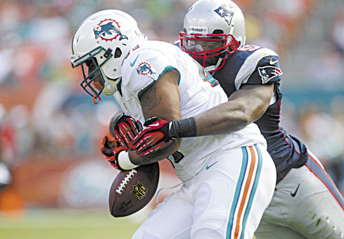 NICE DEFENSE: Miami fullback Jorvorskie Lane fumbles the ball as he is tackled by New England linebacker Jerod Mayo during the first half Sunday in Miami. The Dolphins recovered the ball.