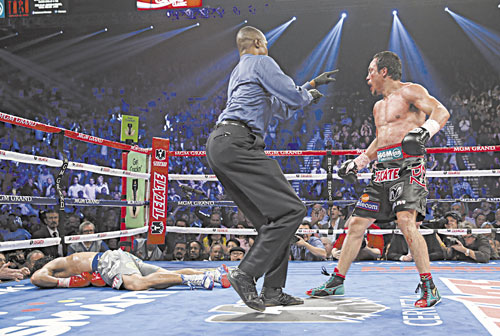 IT'S OVER: Referee Kenny Bayless, center, sends Juan Manuel Marquez, right, to his corner after Marquez knocked out Manny Pacquiao, left, in the sixth round of their WBO world welterweight fight Saturday in Las Vegas. Marquez won the fight by a knockout.