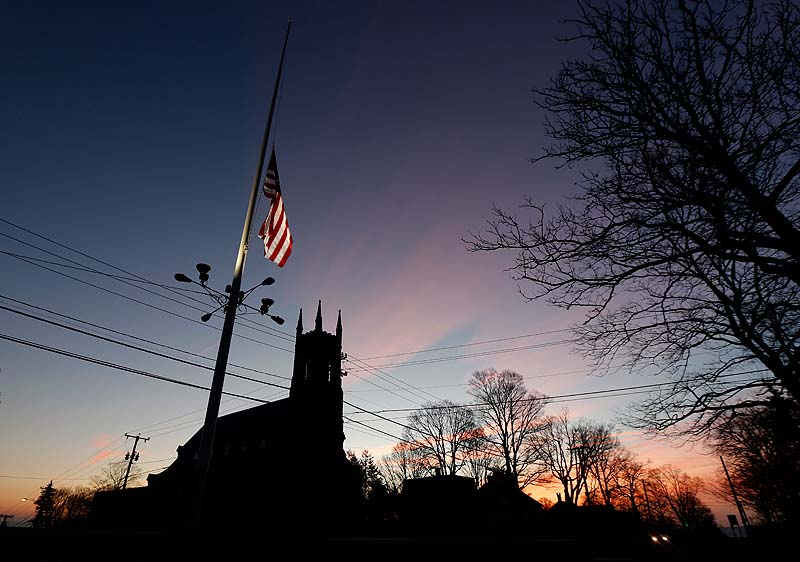 A U.S. flag flies at half-staff as vehicles drive on Main Street in downtown Newtown, Conn., as the sun rises Saturday morning after a gunman opened fire inside a nearby elementary school.