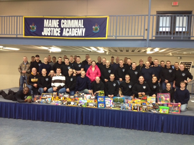 Members of the Maine Criminal Justice Academy's latest graduating class with the gifts they gathered to donate to charity.