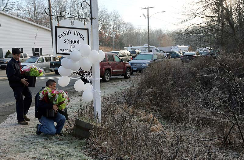 A couple of volunteer firefighters place flowers at a makeshift memorial at a sign for the Sandy Hook Elementary school on Satuday.