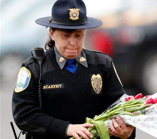 Newtown Police Officer Maryhelen McCarthy places flowers at a makeshift memorial outside St. Rose of Lima Roman Catholic Church on Sunday in Newtown, Conn.