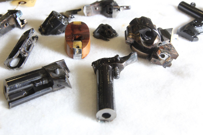 Pieces of destroyed firearms lie on a table at Hammond Tractor Co. in Fairfield on Friday. In the wake of the Newtown, Conn. shooting, Hammond Tractor is offering to accept and destroy firearms.