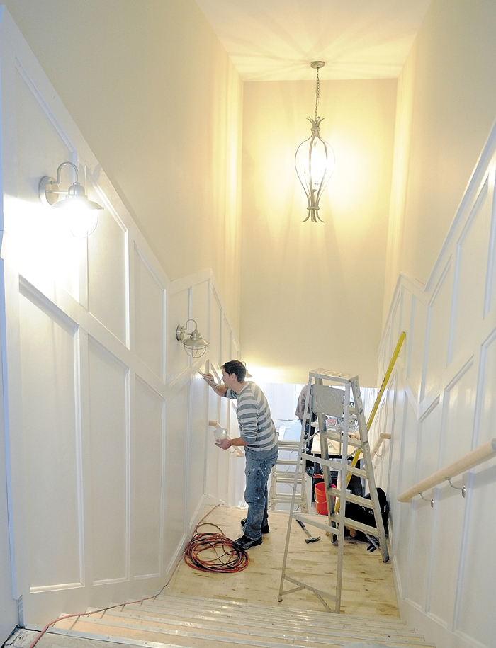 Kris Devine paints the newly installed wooden trim in the public stairway between Water Street and the Arcade parking lot on Dec. 14 in downtown Gardiner. Work is also under way at the top of the stairway, where the former Mad Dog Pub is being renovated and will reopen as Alex Parker's Steak House.