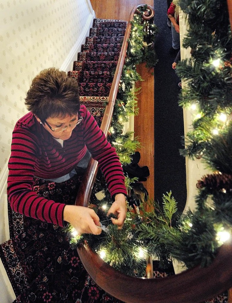 Shelly Hanson, of Chelsea, attaches a snowflake to the garland hanging off the front entryway banister on Tuesday at the Blaine House, in Augusta.