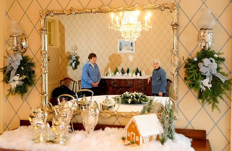 Cynthia Herrick, left, and Jean Wave decorated the family dining room on Tuesday at the Blaine House in Augusta.