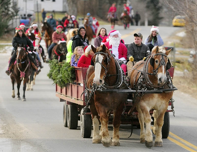 Riding in a wagon, Santa Claus leads the 6th annual Hemphill's Christmas parade down Oak Grove Road on Sunday, in North Vassalboro. The parade started from Hemphill's stables, proceeded down Oak Grove Road to Route 32, went around a block and returned to the farm, where there was a contest for the best costumed horses and riders.