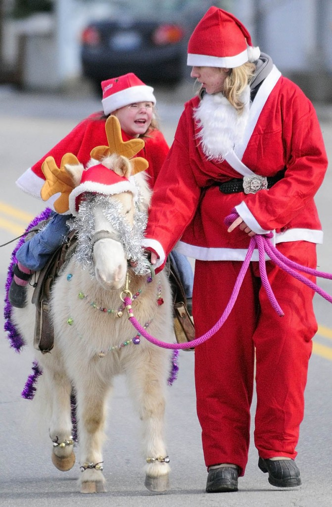 Madyson Beaulieu, left, 4, rides on Flash the pony led by Michele Gatie, 18, both of Smithfield, during the 6th annual Hemphill's Christmas parade on Sunday, on Oak Grove Road in North Vassalboro.