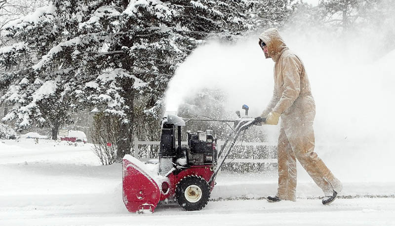 Larry Morrissette clears the driveway with a snow blower Monday morning in Hallowell, where at least 5 or 6 inches of snow had fallen overnight.