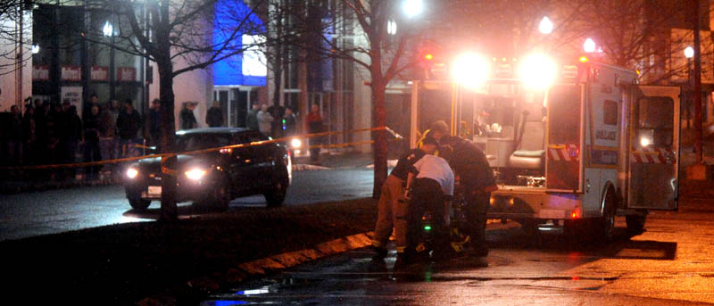 Staff photo by Michael G. Seamans The victim of a shooting is loaded into an ambulance on The Concourse in Waterville late Tuesday night.