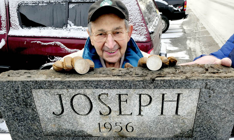 Bill Joseph, 94, stands behind the corner stone of a former beer store he once owned in Fairfield. The stone was removed from a building that will be demolished beside the Gerald Hotel to make room for parking. Under the stone were two silver dollars Joseph is holding.