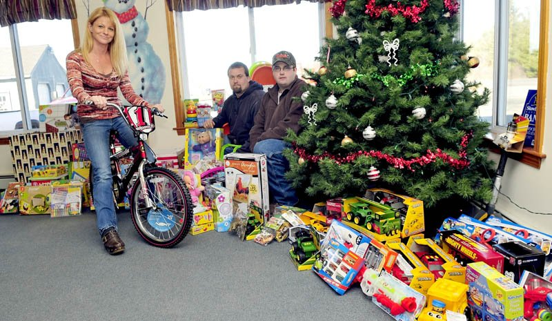 Charlie & Sons Used Cars and Chuck's Auto Recovery & Towing have collected money and toys for Madison area children this holiday season. Inside the Madison business are Kristina Willette, Ken Ashe and owner Charlie Robbins.