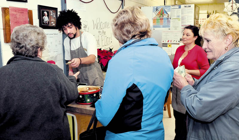 Culinary student Dallas Hutchinson takes payments from people who dined at the popular The Food Place, at Skowhegan Area High School, on Tuesday. Looking on at right is education technician Janelle Saucier.