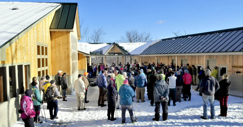 People assemble between the lodge, at left, and the bunk house to listen to speakers during the grand opening of the fourth hut in the Maine Huts and Trails system in Carrabassett Valley on Wednesday.