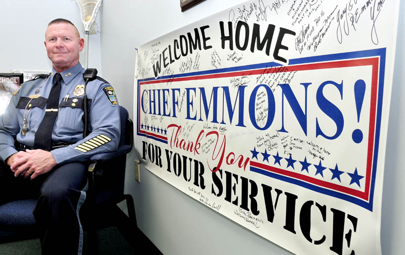Skowhegan Police Chief Michael Emmons sits next to a huge sign in his department office, welcoming him back after a tour of duty in Southwest Asia, on Thursday.