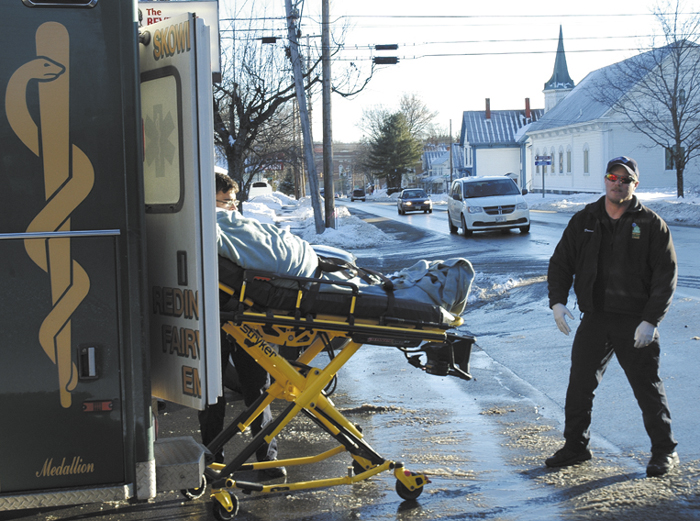Abben Poyington, 24, of Skowhegan, is put into an ambulance with minor injuries Friday after he was struck by a vehicle while walking his bicycle in a parking lot on North Avenue in Skowhegan. An emergency worker stands by.