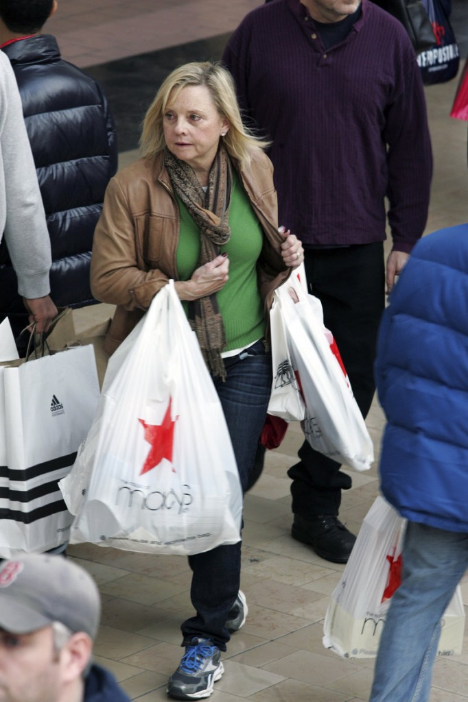 A last-minute Christmas shopper dashes through the Willowbrook Mall in Wayne, N.J., on Sunday. Shoppers seem to be spending less this holiday season, analysts said.