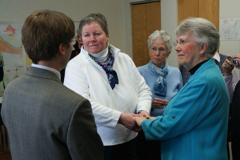 Cathy Meaney, 57, and Anne Merrifield, 73, take marriage vows at Brunswick Town Hall on Saturday. Town Councilor Dan Tucker officiated at the wedding. Their friend Elaine Mower of Brunswick was a witness.