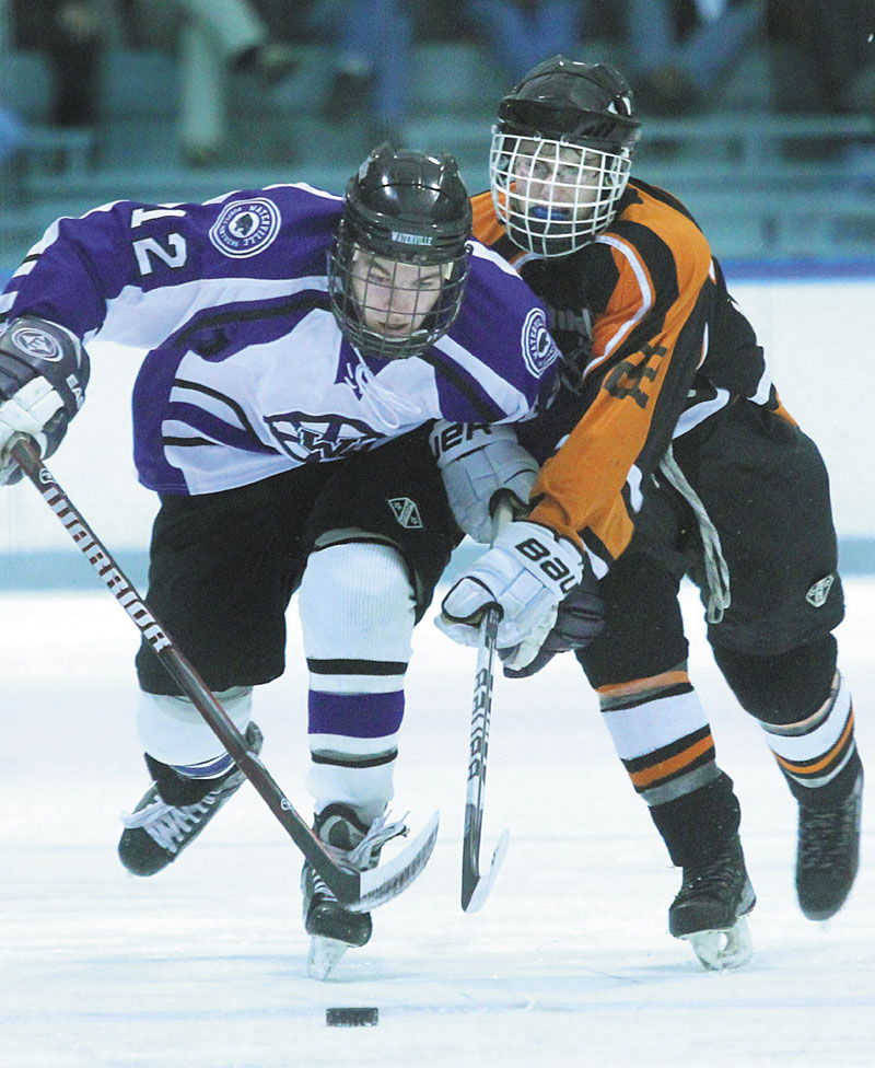 HOLDING HIM BACK: Waterville Senior High School's Tommy Samson holds off Winslow High School's Dameron Rodrigue while skating the puck up ice during the second period Tuesday at Colby College in Waterville.