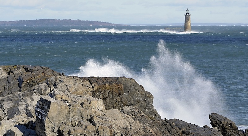 On Thursday, January 31, 2013, the wind blows hard as waves splashing up on the rocks at the Portland Head Light frame Ram Island Ledge Lighthouse and blowing waves.