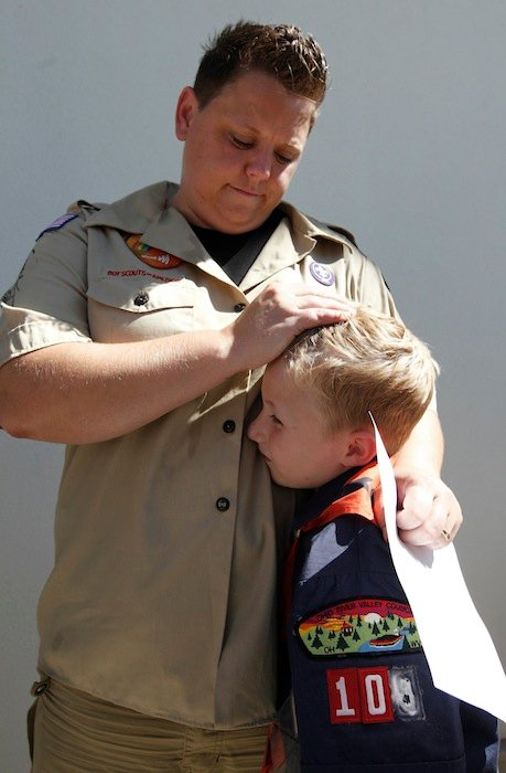 n this July 18, 2012 file photo, Jennifer Tyrrell hugs her son Cruz Burns, 7, outside Boy Scouts national offices in Irving, Texas, after a meeting with representatives of the 102-year-old organization. The Ohio woman was ousted as a den mother because she is a lesbian. The Boys Scouts of America announced Monday, Jan. 28, 2013, that it is considering a dramatic retreat from its controversial policy of excluding gays as leaders and youth members. (AP Photo/LM Otero, File)