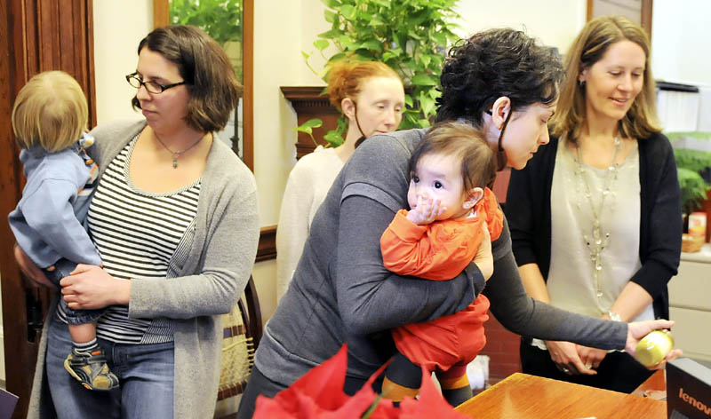 Lilijana Cvetkoska, of Cape Elizabeth, clutches her infant daughter, Olga Malenko, while leaving a can of baby food on the desk of Gov. Paul LePage's receptionist Wednesday during a protest at the State House in Augusta.