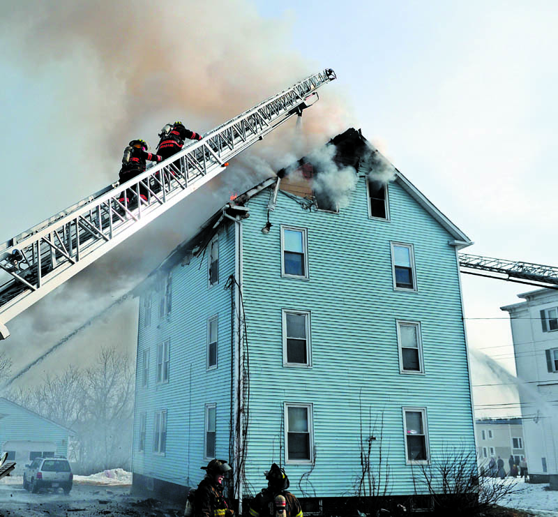 Firefighters attack a blaze Tuesday at 1 Penobscot St. in Augusta, which that damaged the apartment building. Firefighters from several communities fought the fire, but no injuries were reported, according to firefighters.