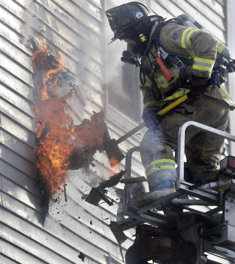 A firefighter exposes an exterior wall Tuesday at 1 Penobscot St. in Augusta. Fire heavily damaged the apartment building.