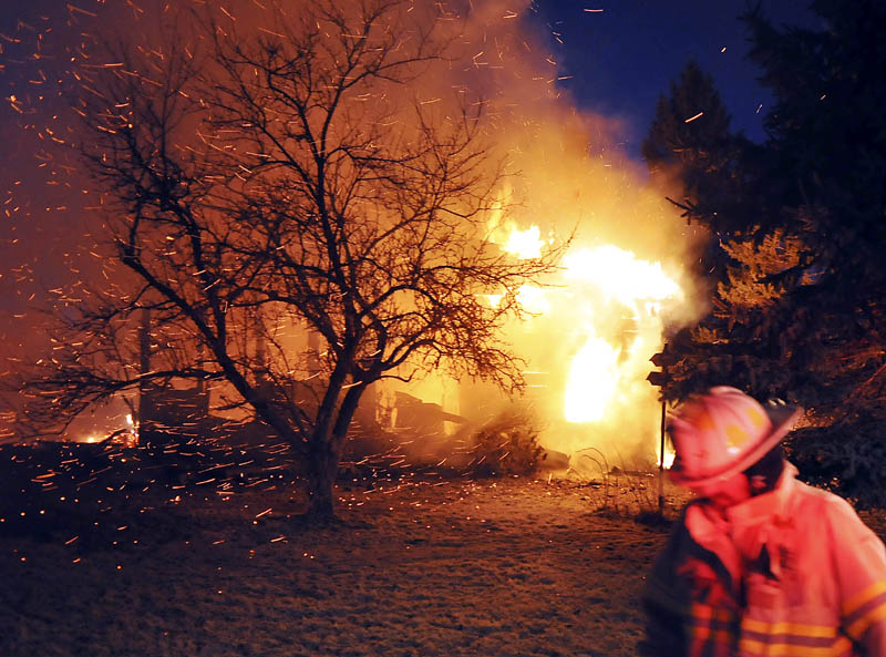 A firefighter walks by the blaze on the Crummett Mountain Road in Somerville Thursday night. Firefighters from several towns were unable to locate the resident of the farmhouse, 92-year-old Cecil Brann.