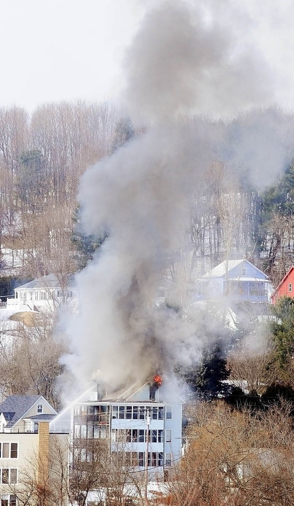 Smoke pours from the roof of 1 Penobscot St. at 12:48 p.m. Tuesday in this photo taken from the east side of Augusta.