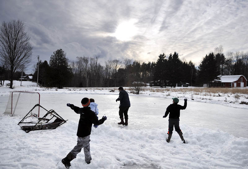Boys pelt Mike Flynn, center, with snowballs on Sunday, on the ice at Lily Pond in West Gardiner. The ice that Flynn was cleaning off with a shovel was too rough for hockey, so the kids resorted to plugging him with snow.