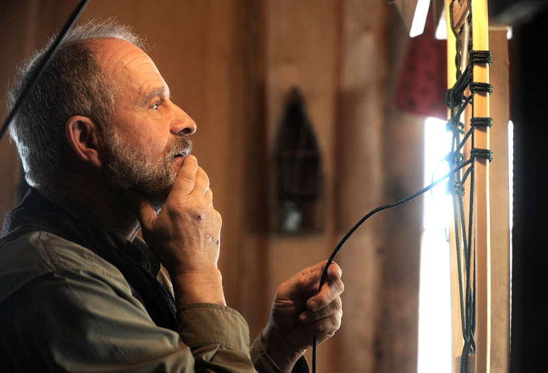 Dave Giampetruzzi, 63, of China, fabricates a snowshoe in his cabin at Pine Grove Lodge in Bingham on Thursday.