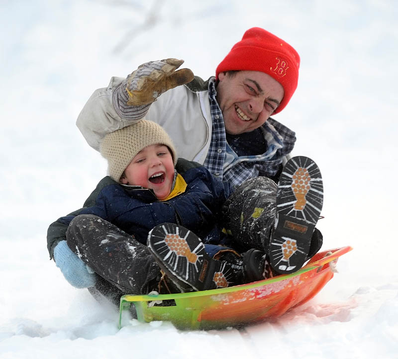 Randy Hawes and his son, Brady, 4, slide down the Sherwin Street hill in Waterville Thursday.