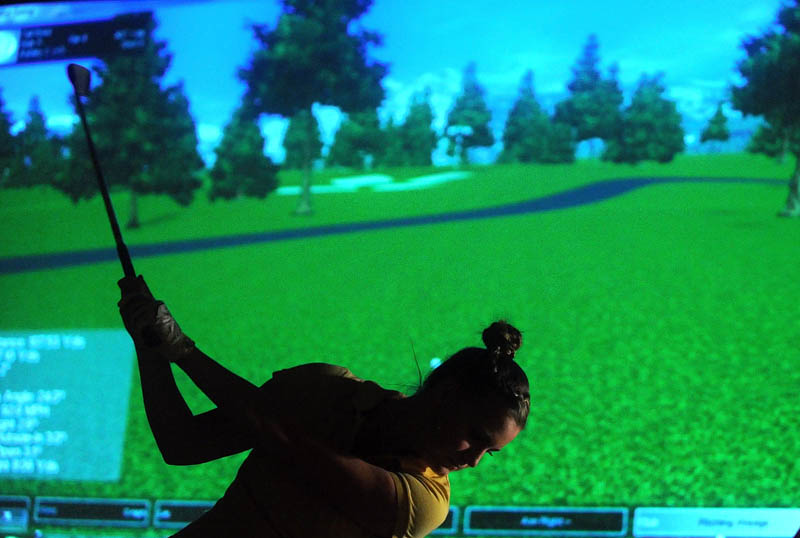Ashley Chubbuck, 17, of Windsor, takes a shot during a round of virtual golf at the Alfond Youth Center on North Street in Waterville on Tuesday. The center's virtual golf program offers 26 courses, along with a driving range and two par-3 holes. Virtual golf is open to the public Tuesday and Thursdays, from 10 a.m. to 2 p.m., and 6 p.m. to 9 p.m.