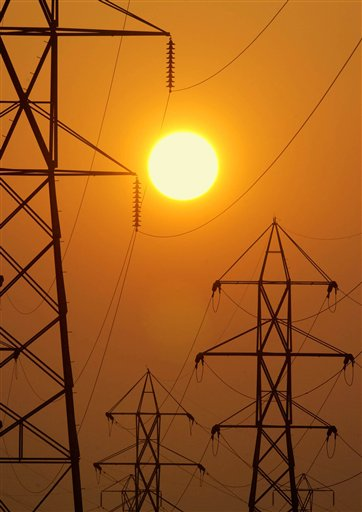 In this Sepember 2003 file photo, the setting sun silhouettes electric transmission lines. New England's power grid operator says wholesale electricity prices dropped by nearly 23 percent regionally last year thanks to falling natural gas prices and decreased demand. (AP Photo/Mark Duncan, File)