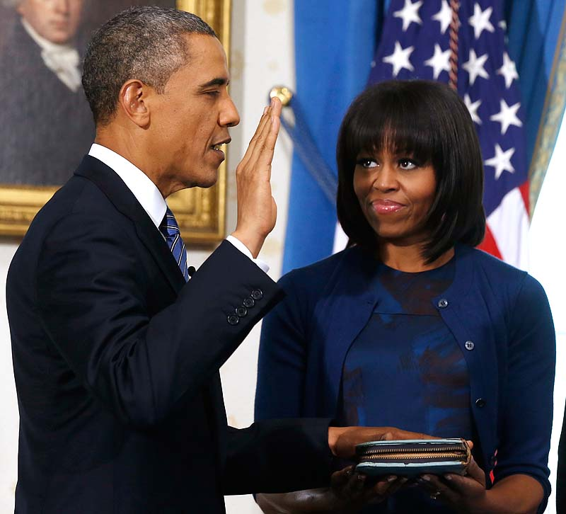 President Barack Obama is officially sworn in by Chief Justice John Roberts in the Blue Room of the White House during the 57th Presidential Inauguration in Washington on Sunday, as first lady Michelle Obama, holds the Robinson Family Bible.
