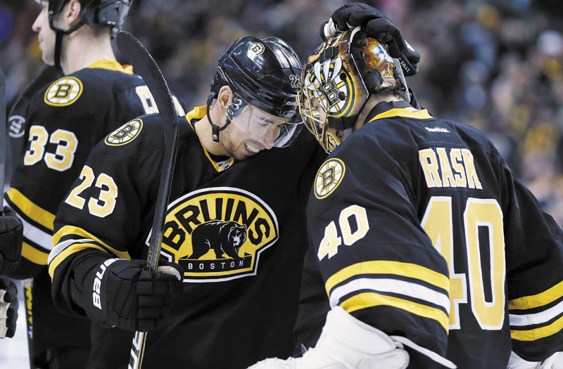 NICE WIN: Boston's Chris Kelly (23) celebrates with goalie Tuukka Rask after the Bruins defeated the Winnipeg Jets 2-1 in a shootout Monday in Boston.