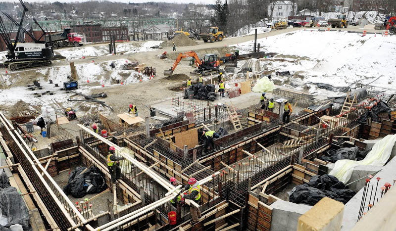 Workers build concrete forms in the foreground as pile driving continues on Tuesday at construction site for the Kennebec County court houses.