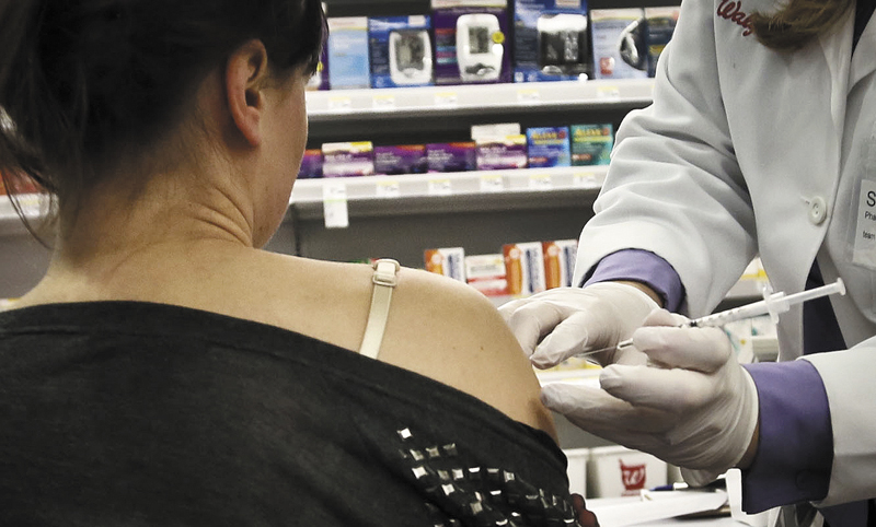 Pharmacist Stacia Woodcock, a pharmacy manager for Walgreens in New York, administers a flu vaccine Monday.