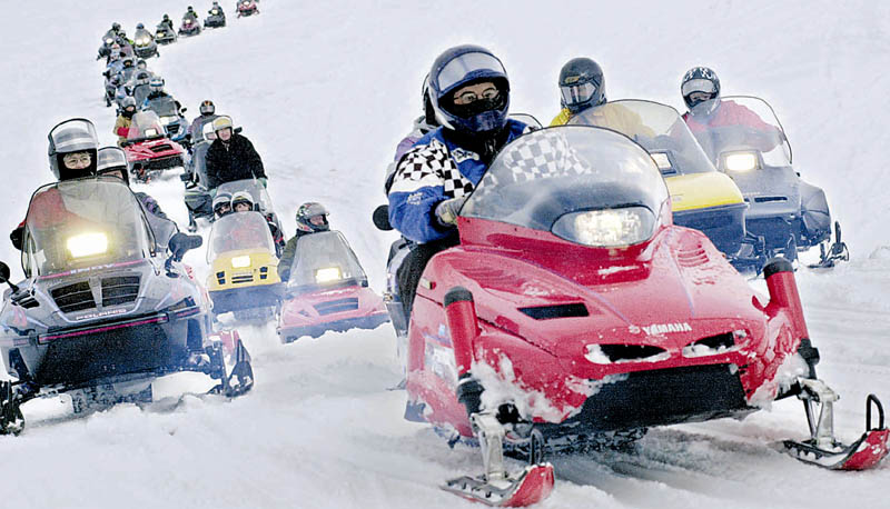A parade of snowmobiles makes its way across Sebasticook Lake in Newport. Riders are being urged to use caution, especially around early season hazards, such as unstable ice.