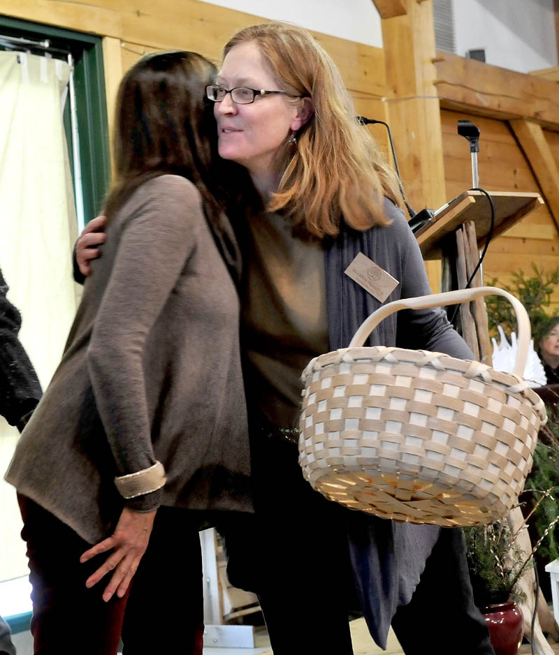 Maine Organic Farmers and Gardeners Association interim executive director Heather Spalding, right, accepts a Native American basket from Theresa Secord, of Waterville, during a memorial celebration for Russell Libby, in Unity on Sunday.