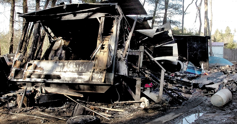 The charred remains of a mobile home where Robert and Kelley Robinson and their children escaped after fire quickly took over Tuesday on Smithfield Road in Norridgewock. Fire also damaged another home in town earlier Tuesday.