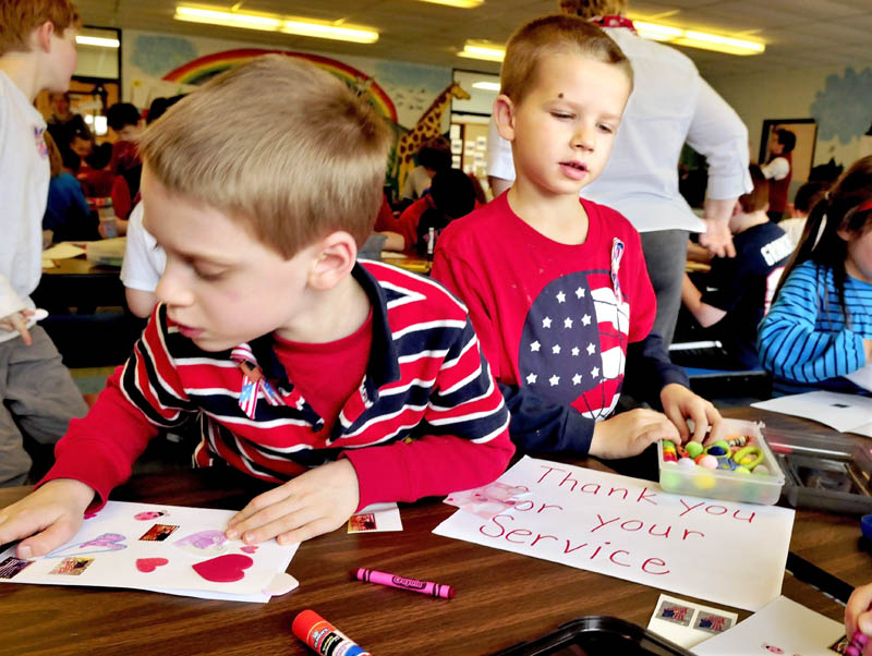 St. John Catholic School students Parker Hunter, left, and Aidan Veilleux work on Valentines for Veterans at the Winslow school on Thursday.