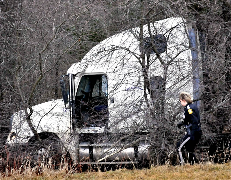 Fairfield police officer Shana Blodgett investigates a tractor trailer truck that went into a wooded section of U.S. Route 201 in Fairfield following a collision with a department cruiser that left officer Bill Beaulieu injured on Thursday.