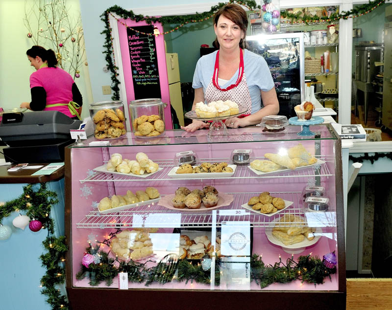 Sharalyn Albertson stocks a display case with baked goods she and Janet Johnson, left, make, recently at the Blessed Life Bakery in Waterville.