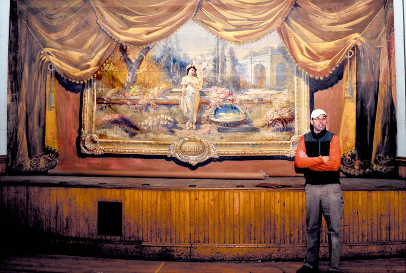 Builder Stephen Dionne speaks about restoring the former Skowhegan Grange in front of a hand-painted curtain, on the stage in the Grand Assembly Room, on Wednesday.